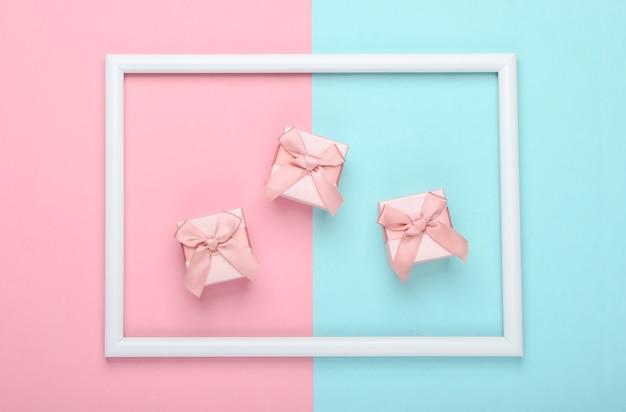 Coffrets cadeaux sur surface pastel bleu rose avec cadre blanc