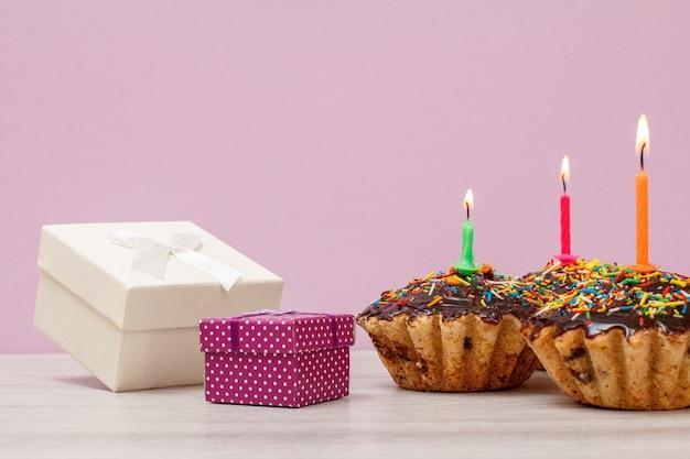 Coffrets cadeaux et trois délicieux muffins d'anniversaire avec glaçage au chocolat et caramel, décorés de bougies festives allumées sur fond lilas. concept minimal de joyeux anniversaire.