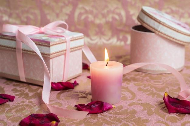 Coffrets roses avec une bougie sur des pétales de rose