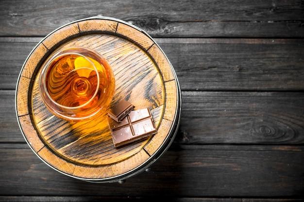 Cognac dans un verre avec du chocolat sur un tonneau. sur bois noir