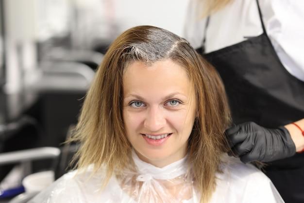 Coiffeur, application de teinture capillaire sur les cheveux avec une brosse