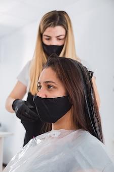 Le coiffeur applique de la crème colorée sur les cheveux - le coiffeur avec des gants noirs teint les cheveux d'une femme.