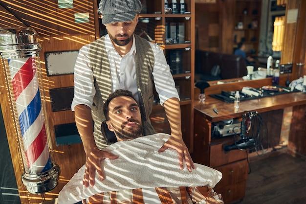 Un coiffeur attentionné met une serviette propre sur la poitrine de son client avant de se mettre au travail avec ses cheveux