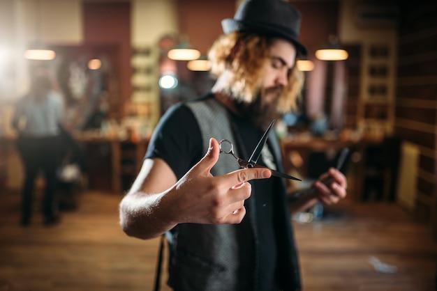 Coiffeur barbu brutal en chapeau pose avec des ciseaux à la main