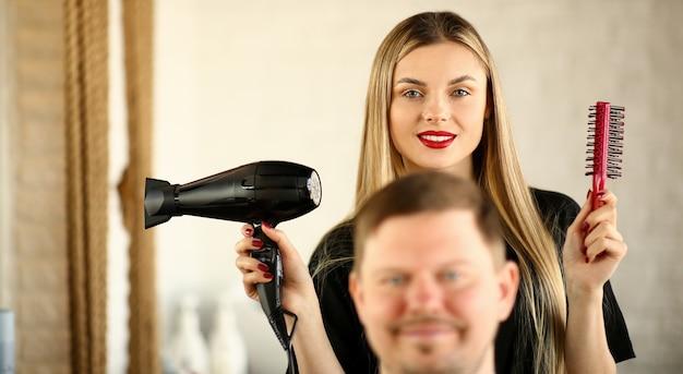 Coiffeur blond à l'aide d'un sèche-cheveux et d'un peigne pour homme
