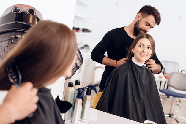 Le coiffeur coiffe la jeune femme aux cheveux bruns.