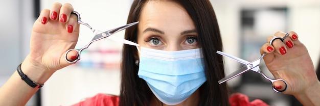 Coiffeur en costume et masque de protection regarder et tenir des ciseaux dans la main gauche et la main droite