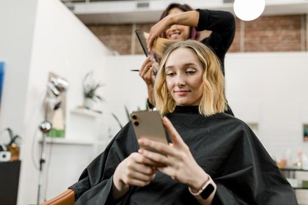 Coiffeur coupant les cheveux du client dans un salon de beauté
