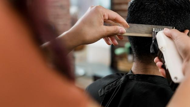 Coiffeur coupant les cheveux du client dans un salon de coiffure