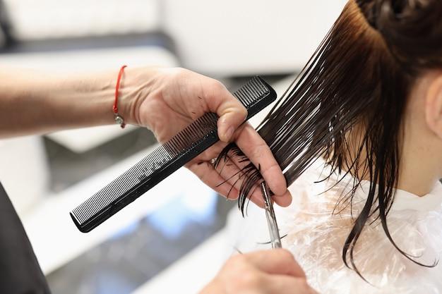 Le coiffeur coupe les cheveux des clients avec des ciseaux