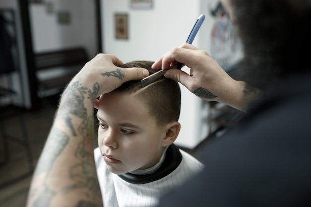 Coiffeur coupe les cheveux du petit garçon