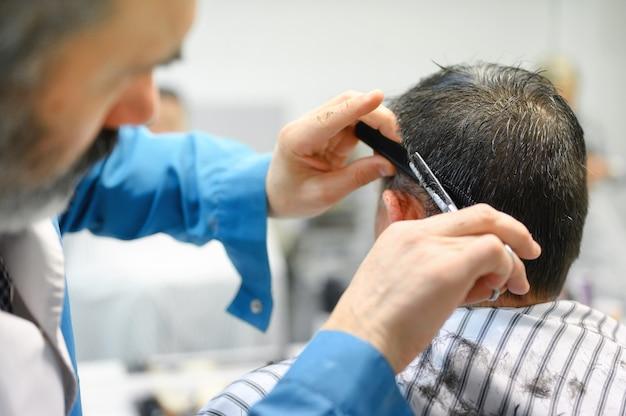 Coiffeur coupe les cheveux du vieil homme au salon de coiffure.