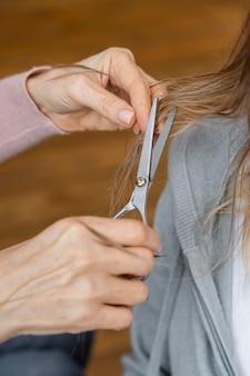 Coiffeur coupe les cheveux de la femme à la maison