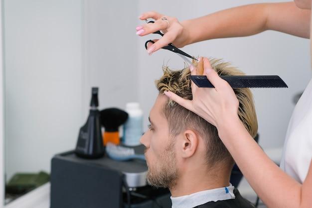 Le coiffeur coupe les cheveux d'un jeune homme aux cheveux teints en blond avec des ciseaux dans un salon de beauté. soins capillaires professionnels.
