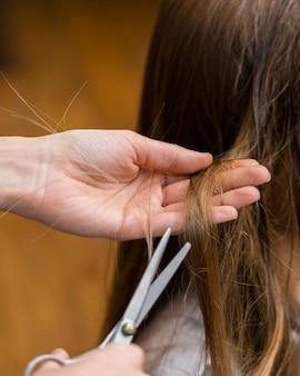 Coiffeur coupe les cheveux de la petite fille