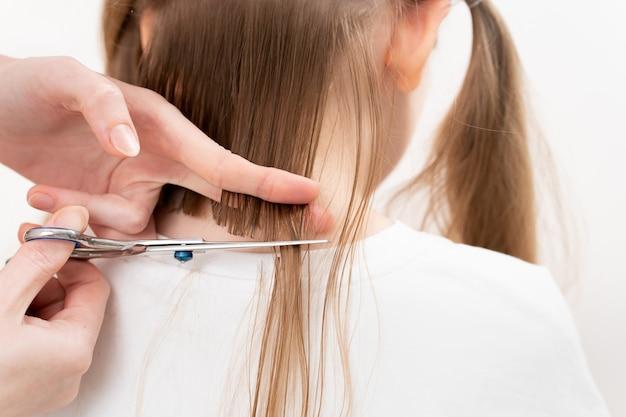 Coiffeur couper les cheveux d'une petite fille