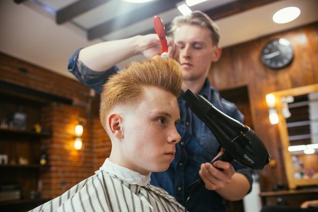 Coiffeur de coupes de cheveux garçon adolescent rousse dans le salon de coiffure. coiffure rétro élégante à la mode. portrait d'un enfant avec une belle coupe de cheveux. ,