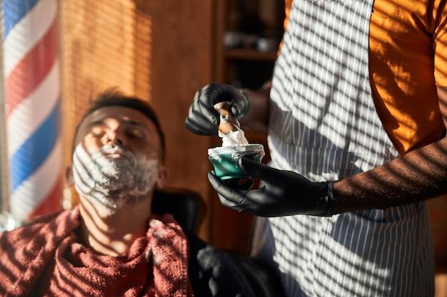 Coiffeur dans des gants stériles préparant la crème à raser dans le salon de coiffure