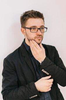 Coiffeur dans une veste noire et une chemise bleue touche son visage par sa main.