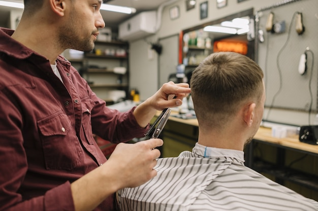Coiffeur donnant une coupe de cheveux à un client