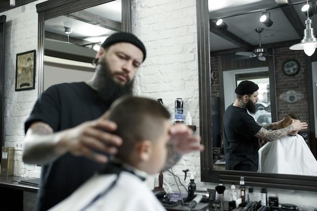 Coiffeur enfants coupe petit garçon dans un salon de coiffure