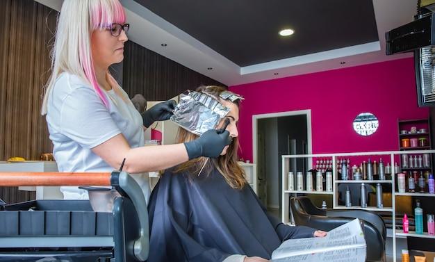 Coiffeur enveloppant des mèches de cheveux avec du papier d'aluminium pour une belle jeune femme en lisant un magazine