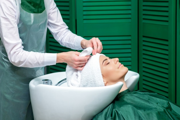 Le coiffeur enveloppe les cheveux du client dans une serviette.