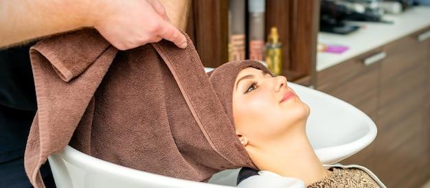Coiffeur enveloppe la tête de client féminin avec une serviette dans l'évier dans un salon de coiffure