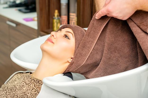 Coiffeur enveloppe la tête du client féminin avec une serviette dans l'évier dans un salon de coiffure