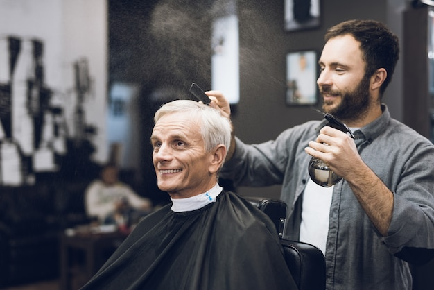 Coiffeur faisant coiffure homme âgé