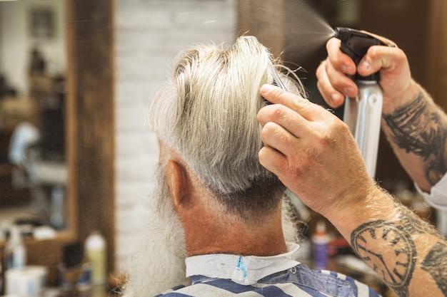 Coiffeur faisant une coupe de cheveux élégante pour un beau vieil homme dans le salon de coiffure