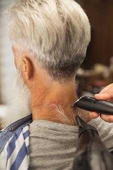 Coiffeur faisant une coupe de cheveux élégante pour vieil homme dans le salon de coiffure