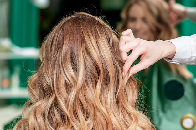 Le coiffeur fait la coiffure frisée pour la femme dans le salon de beauté, vue arrière.