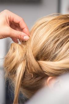 Le coiffeur fait la coiffure de la jeune femme