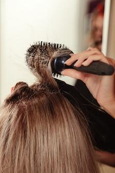 Coiffeur fait coiffure jolie jeune femme dans un salon de beauté. le service client dans la salle intérieure crée une image incroyable. assistant de création de coiffures de travail. concept de mode de vie sain et de bien-être