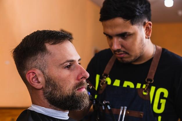 Le coiffeur fait la coupe de cheveux pour le client dans la boutique du coiffeur