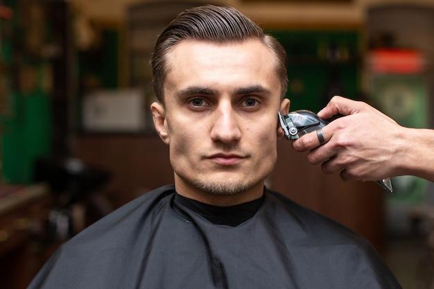 Un coiffeur fait une coupe de cheveux