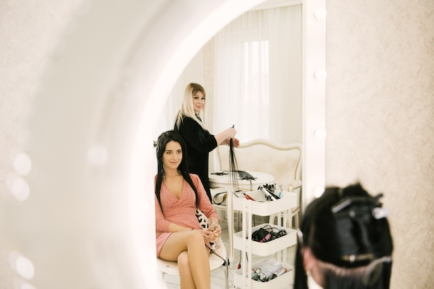 Le coiffeur fait des extensions de cheveux à une jeune femme dans un salon de beauté
