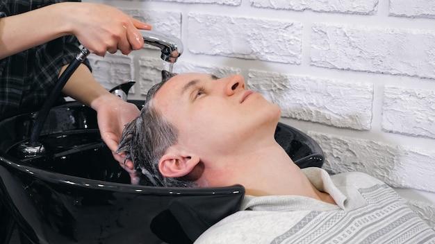 Le coiffeur féminin lave un homme principal dans le salon de coiffure, plan rapproché