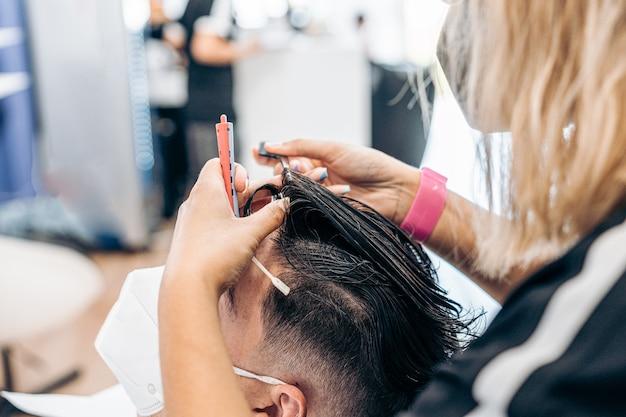 Coiffeur féminin peignant les cheveux d'un homme se faisant couper les cheveux dans un salon de coiffure