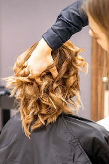 Coiffeur féminin vérifie la coiffure frisée brune d'une jeune femme de race blanche dans un salon de beauté.