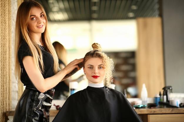 Coiffeur femme et client avec coiffure frisée