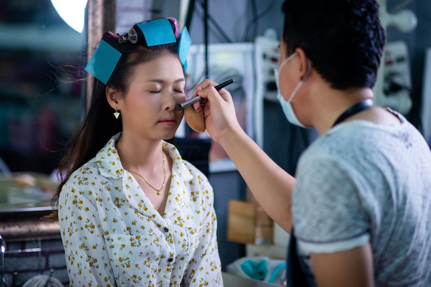 Coiffeur femme debout, maquillage pour le visage et faire coiffure à jolie belle jeune femme dans un salon de beauté