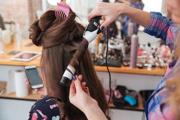 Coiffeur de femme faisant la coiffure utilisant le fer à friser pour les cheveux longs de la jeune femme avec le smartphone dans le salon de beauté