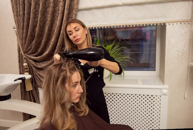 Coiffeur femme mature blonde séchant les cheveux blonds du client avec un sèche-cheveux dans un salon de beauté