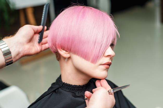 Le coiffeur a fini de faire une coiffure courte rose