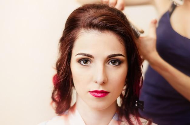 Coiffeur fonctionne. styliste torsade cheveux repasser à la jeune fille aux cheveux rouges.