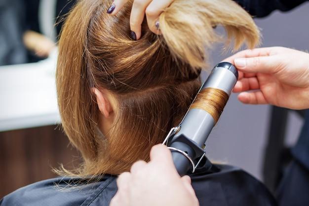 Coiffeur frisant de longs cheveux châtain clair