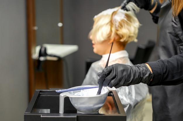 Coiffeur en gants noirs teint les cheveux de la jeune femme en couleur blanche dans un salon de coiffure