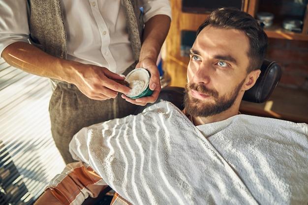Un coiffeur habile mélangeant une crème à raser pour un jeune homme dans un fauteuil